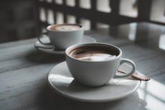 Deux tasses blanches de café chaud sur la table en café Photo stock