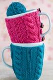 Deux tasses bleues dans le chandail bleu et rose avec la boule du fil pour le tricotage Photo stock