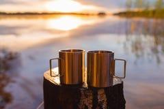 Deux tasses campantes ou tasses d'acier inoxydable sur un tronçon en bois contre un lever de soleil dramatique ou le soleil par u photo stock