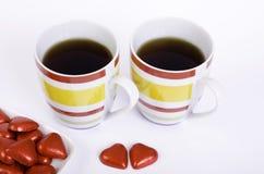 Deux tasses coeurs de thé et de chocolat Photos stock