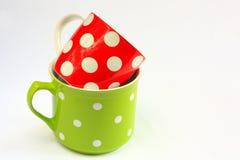 Deux tasses colorées avec les points de polka blancs Photo libre de droits
