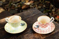 Deux tasses colorées vides après avoir bu du café sur une table en bois Photos stock