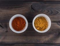 Deux tasses d'épices, de paprika et de safran des indes sur la table en bois Images libres de droits