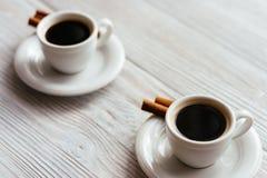 Deux tasses d'expresso avec des bâtons de cannelle sur une table en bois blanche Photographie stock libre de droits
