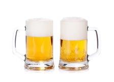 Deux tasses de bière sur un fond blanc Images stock