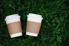 Deux tasses de café à aller sur l'herbe Images libres de droits