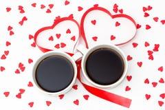 Deux tasses de café attachées avec un ruban rouge sous forme de coeurs et beaucoup de petits coeurs sur un fond blanc Photos libres de droits