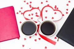 Deux tasses de café attachées avec un ruban rouge sous forme de coeurs et deux du journal intime sur un fond blanc Photographie stock libre de droits