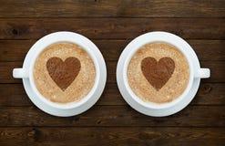 Deux tasses de café avec des coeurs sur le bois Photographie stock