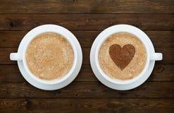 Deux tasses de café avec des coeurs sur le bois Photo libre de droits