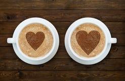 Deux tasses de café avec des coeurs sur le bois Images stock