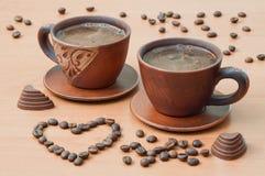Deux tasses de café avec des grains de café sous forme de coeur dessus Images stock
