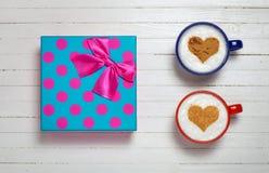 Deux tasses de café avec le coeur forment le symbole et le boîte-cadeau Images stock