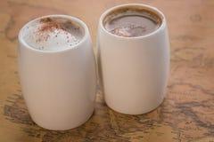 Deux tasses de café blanches se tiennent sur une carte du monde sur un fond léger Photo stock