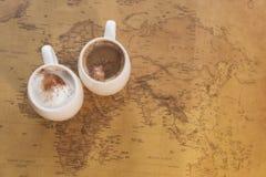 Deux tasses de café blanches se tiennent sur une carte du monde sur un fond léger Photographie stock libre de droits