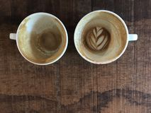 Deux tasses de café chaud de finition de latte avec l'art de surplus de latte Image libre de droits