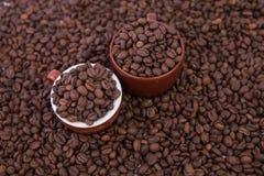 Deux tasses de café complètement des grains de café Plan rapproché Photos stock