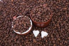 Deux tasses de café complètement des grains de café Plan rapproché Image libre de droits