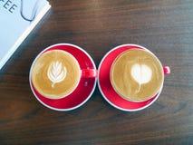 Deux tasses de café d'art de latte sur la table en bois Image libre de droits