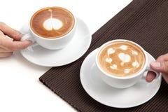 Deux tasses de café d'endroit de forme de coeur d'art de latte sur la serviette sur le petit morceau Photo libre de droits