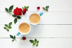 Deux tasses de café d'expresso et roses de rouge fleurit sur le fond blanc Photographie stock libre de droits
