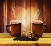 Deux tasses de café, de cannelle et de grains de café chauds Communication images stock
