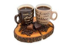 Deux tasses de café, de coeurs de chocolat et de grains de café sur le tronçon Image libre de droits