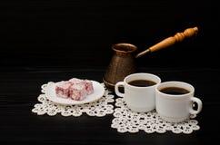 Deux tasses de café, de plaisir turc et de pots de cerise sur un fond noir Photographie stock libre de droits