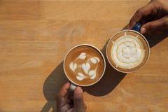 Deux tasses de café différent qui sont lait de latte de cappuccino et de caramel se tenant à la main des amis sur la table rustiq photo stock