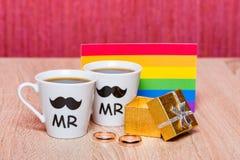 Deux tasses de café, de drapeau gai et d'un boîte-cadeau avec le mariage sonnent Photographie stock libre de droits