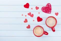 Deux tasses de café et de coeurs mélangés sur la vue supérieure bleue en pastel de table Petit déjeuner de matin pour le jour de  Image libre de droits