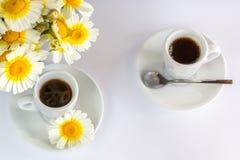 Deux tasses de café et d'un bouquet des camomiles Images stock