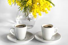 Deux tasses de café et d'un vase de branches de mimosa sur un fond blanc Images libres de droits