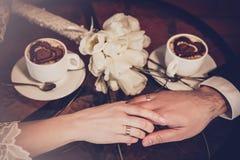 Deux tasses de café et de la main des jeunes mariés Photo libre de droits