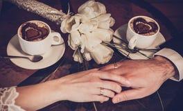 Deux tasses de café et de la main des jeunes mariés Images stock