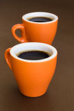 Deux tasses de café modernes sur une surface brune Photo stock