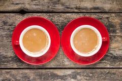 Deux tasses de café rouges avec du lait sur le vieux fond en bois. Photographie stock