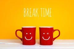 Deux tasses de café rouges avec visages de sourire sur un fond jaune Images stock