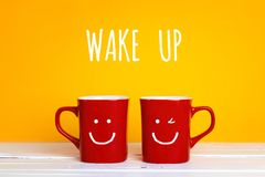Deux tasses de café rouges avec visages de sourire sur un fond jaune Photos stock