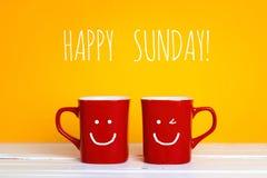 Deux tasses de café rouges avec visages de sourire sur un fond jaune Image libre de droits