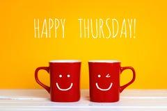 Deux tasses de café rouges avec visages de sourire sur un fond jaune Photographie stock libre de droits