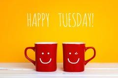 Deux tasses de café rouges avec visages de sourire sur un fond jaune Images libres de droits