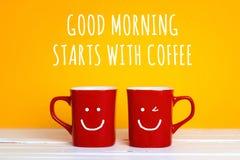 Deux tasses de café rouges avec visages de sourire sur un fond jaune Photo stock
