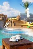 Deux tasses de café sur la table près de la piscine Images stock