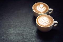 Deux tasses de café sur le fond rustique noir Images stock