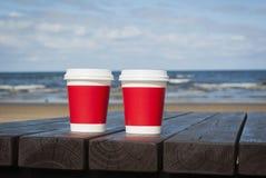 Deux tasses de café sur le littoral échouent pour un couple dans l'amour Photos libres de droits