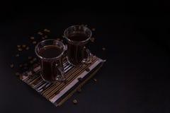 Deux tasses de café sur le tissu avec des haricots de coffe Photographie stock libre de droits