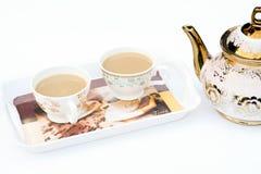 Deux tasses de café sur un plateau et près d'une bouilloire avec le fond blanc couleur Photos libres de droits