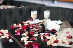 Deux tasses de café sur une table répandue avec des pétales Le type a juste admis son amour à son amie Photos stock