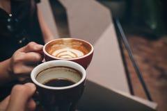 Deux tasses de café tintantes de personnes en café moderne Images stock